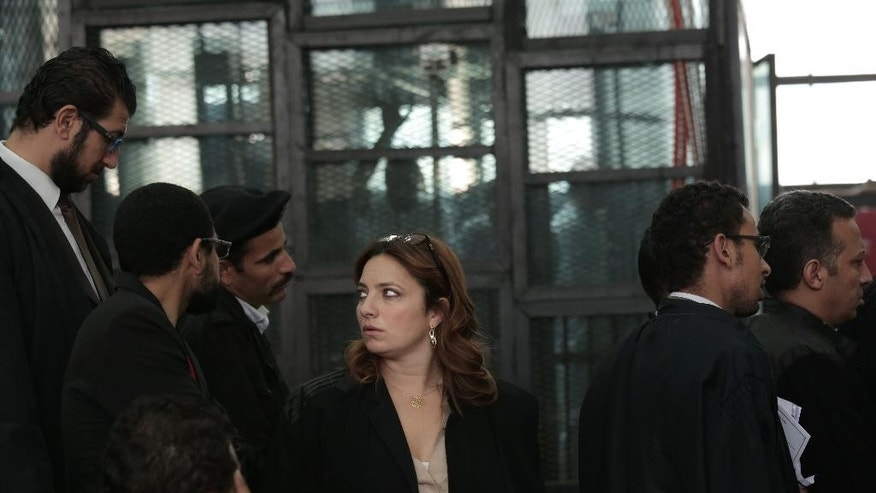 In this Thursday, Dec. 4, 2014 photo, Egyptian lawyer Ragia Omran, center, waits to speak during a trial session of activists facing charges on organizing unauthorized protests, at a courtroom in Cairo, Egypt. The 41-year-old Omran standing only 5 feet tall (1.5 meters) charges with determined steps into prisons, police stations and courtrooms. She earns her living as a corporate lawyer. Defending activists is her volunteer work. That can mean punishing hours. One recent day, she attended the signing of a nearly $1 billion loan deal that her firm managed, then over the days that followed, she was in court representing jailed activists, tromping into police stations to find clients, and visiting prisons, trying to bring food and other supplies to detainees. (AP Photo/Nariman El-Mofty)