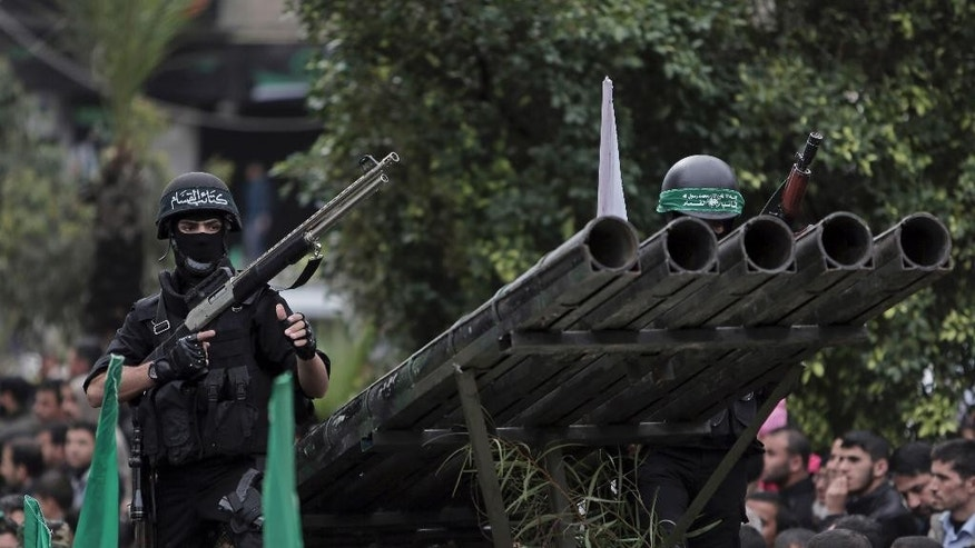 Palestinian Hamas masked gunmen display their military skills during a rally to commemorate the 27th anniversary of the Hamas militant group, in Gaza City, Sunday, Dec. 14, 2014. (AP Photo/Khalil Hamra)