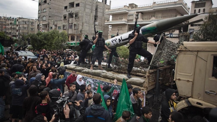 Palestinian Hamas masked members parade in a rally to commemorate the 27th anniversary of the Hamas militant group, in Gaza City, Sunday, Dec. 14, 2014. (AP Photo/Khalil Hamra)