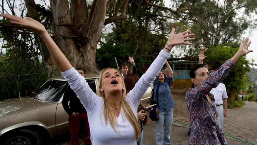 "FILE - In this Nov. 15, 2014, file photo, Lilian Tintori, wife of opposition leader Leopoldo Lopez, left, and his mother, Antonieta Mendoza, look up to his cell and wave to him from the outer perimeters of the Ramo Verde prison, in Los Teques, Venezuela. Tintori was hoping for a visit with her husband, but was refused entry. On a recent visit to the prison, Tintori caught sight of her husband from a distance, making out his long figure waving from his prison bars. He was keeping his balance by clinging to the window bars, giving him the appearance of a man just hanging on. ""Hello, beautiful!"" he called out. (AP Photo/ Alejandro Cegarra, File)"