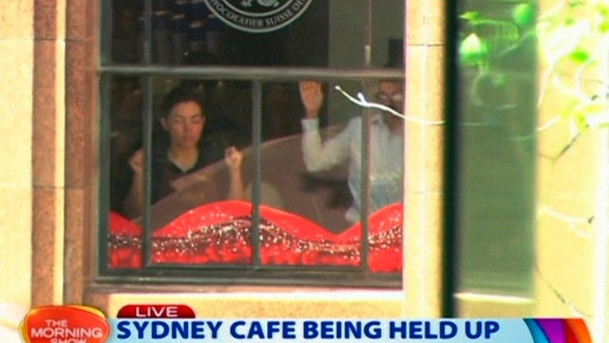 This image taken from video shows people holding up hands inside a cafe in Sydney, Australia Monday, Dec. 15, 2014. A gunman took an unknown number of people hostage inside the downtown Sydney chocolate shop and cafe at the height of Monday morning rush hour, with two people inside the cafe seen holding up a flag believed to contain an Islamic declaration of faith. (AP Photo/Channel 7 via AP Video) AUSTRALIA OUT