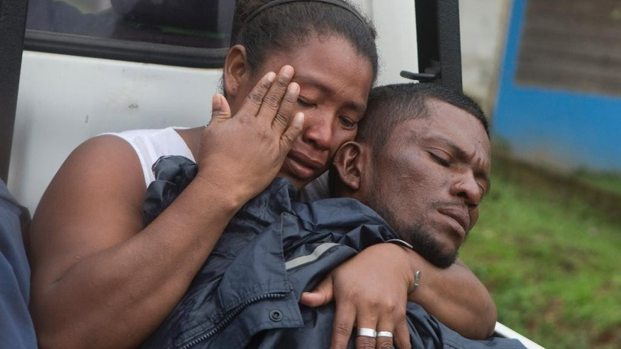 Rescued diver Gerardo Zamora, right, is held by family member as he's taken to a hospital in the back of a truck after being rescued from a shipwreck in Puerto Cabezas, also known as Bilwi, in Nicaragua, Saturday, Dec. 13, 2014. Nicaraguan authorities are searching for 18 fishermen still missing since their ship with 50 people aboard capsized in the Caribbean four days ago. Their lobster boat was on a 15-day trip when it was hit by the wave on Tuesday. (AP Photo/Esteban Felix)