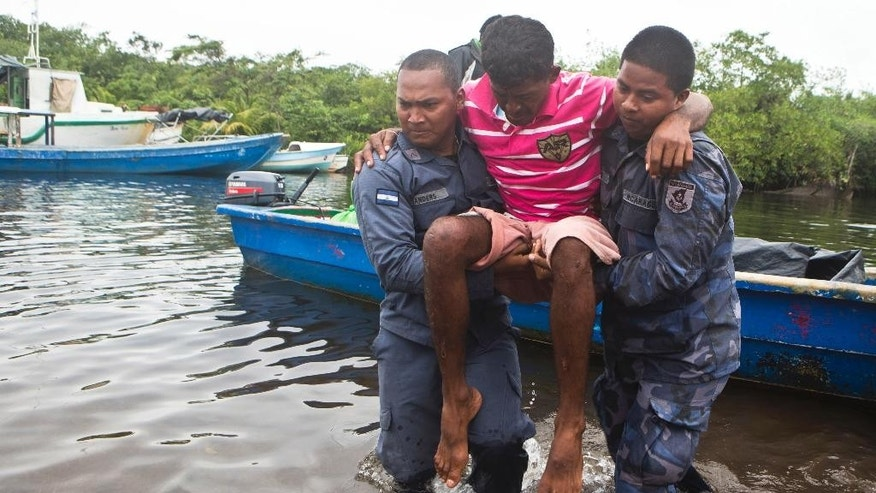 Rescued diver Roberto Mudi is carried by Navy soldiers after he was rescued from a shipwreck, in Puerto Cabezas, also known as Bilwi, in Nicaragua, Saturday, Dec. 13, 2014. Nicaraguan authorities are searching for 18 fishermen still missing since their ship with 50 people aboard capsized in the Caribbean four days ago. Their lobster boat was on a 15-day trip when it was hit by the wave on Tuesday. (AP Photo/Esteban Felix)