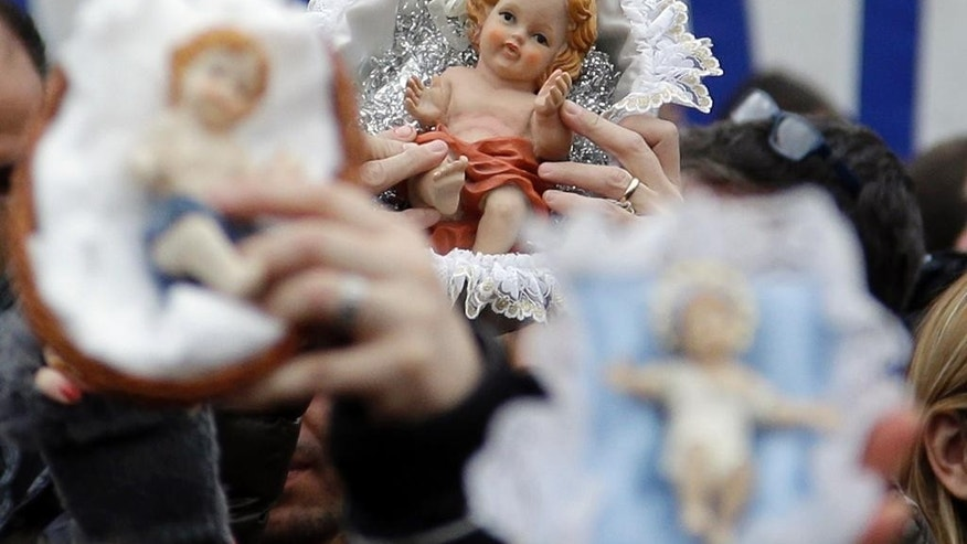 Faithful hold statuettes of baby Jesus, as they listen to Pope Francis delivering the Angelus noon prayer, in St. Peter's Square at the Vatican, Sunday, Dec. 14, 2014. (AP Photo/Gregorio Borgia)