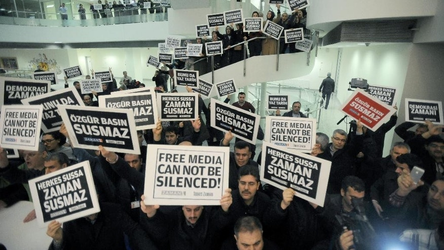 "People gather in support inside the headquarters of Zaman newspaper in Istanbul, Turkey, Sunday, Dec. 14, 2014, hours after police launched raids in a dozen cities, detaining around 20 people including journalists, television producers and police known to be close to a movement led by a U.S.-based moderate Islamic cleric Fethullah Gulen. The government accuses the Gulen's movement, a former ally, of orchestrating an alleged plot to try and bring down the government. It says the group's followers were behind corruption allegations that last year forced four ministers to resign. The placards read: ""Free media cannot be silenced!"" (AP Photo)"