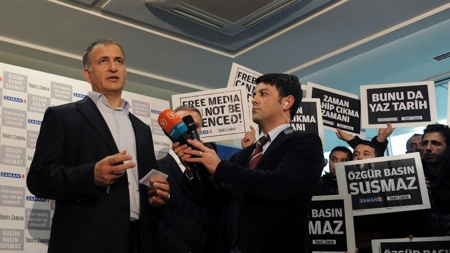 "Ekrem Dumanli, editor-in-chief of  Zaman newspaper, speaks to the media in his office in Istanbul, Turkey, Sunday, Dec. 14, 2014, hours after police launched raids in a dozen cities, detaining over 20 people, including journalists, television producers and police known to be close to a movement led by a U.S.-based moderate Islamic cleric Fethullah Gulen. The government accuses the Gulen's movement, a former ally, of orchestrating an alleged plot to try and bring down the government. It says the group's followers were behind corruption allegations that last year forced four ministers to resign. The placards read: ""Free media cannot be silenced!"" (AP Photo)"