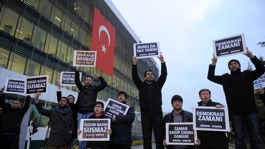 "People gather in support outside Zaman newspaper in Istanbul, Turkey, Sunday, Dec. 14, 2014, hours after police launched raids in a dozen cities, detaining around 20 people including journalists, television producers and police known to be close to a movement led by a U.S.-based moderate Islamic cleric Fethullah Gulen. The government accuses the Gulen's movement, a former ally, of orchestrating an alleged plot to try and bring down the government. It says the group's followers were behind corruption allegations that last year forced four ministers to resign. The placards read: ""Free media cannot be silenced!"" (AP Photo)"