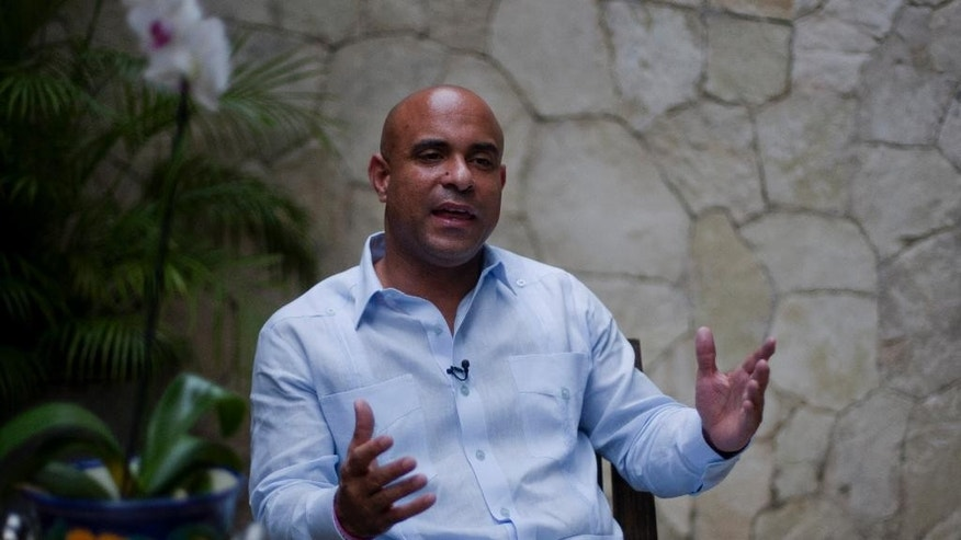 Former Haitian Prime Minister Laurent Lamothe speaks during an interview with Associated Press in Port-au-Prince, Haiti, Monday, Dec. 15, 2014. Lamothe resigned early Sunday. An independent commission had called for his resignation to end a standoff in the Senate that blocked legislation needed to hold parliamentary elections. ( AP Photo/Dieu Nalio Chery)