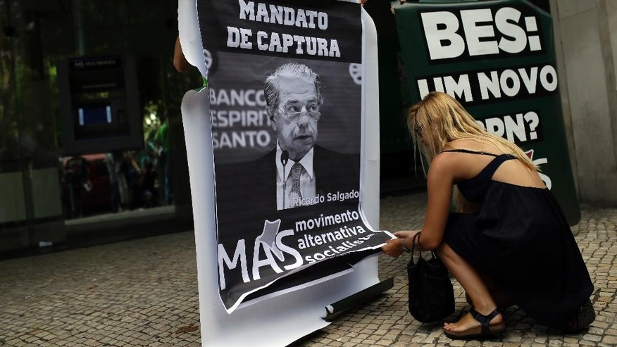 "In this photo taken on Saturday, Aug. 9, 2014, a woman unrolls a poster with a photograph of Ricardo Salgado, former chief executive of Portuguese bank Banco Espirito Santo, recently renamed Banco Novo, during a small protest outside the bank's headquarters in Lisbon. The poster reads in Portuguese: ""Arrest warrant"". An investigation by Portugal's Parliament into last summer's collapse _ and 4.9 billion euro ($6 billion) bailout _ of the country's largest listed bank has turned into gripping television as members of the wealthy Espirito Santo banking dynasty wash their dirty laundry in public. (AP Photo/Francisco Seco)"