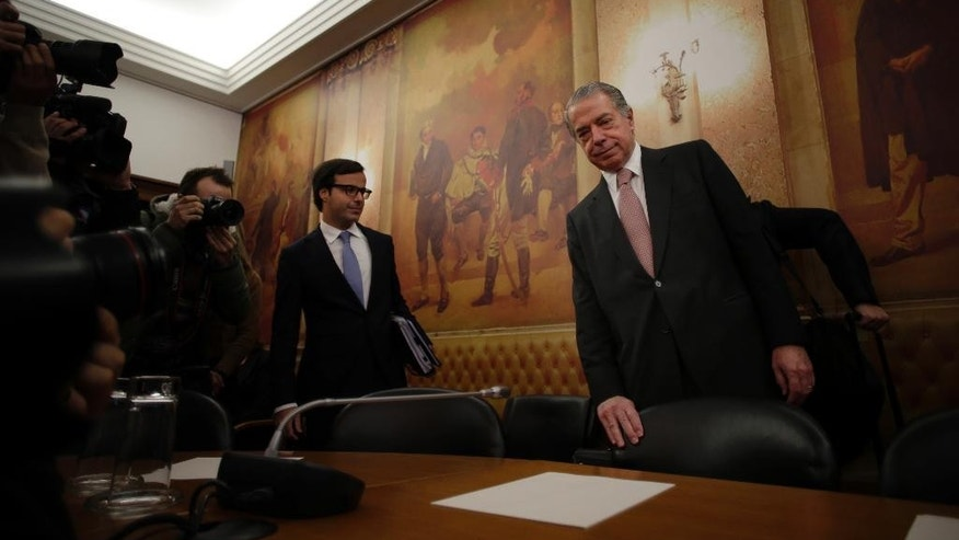 In this photo taken on Tuesday, Dec. 9, 2014, Ricardo Salgado, centre, former chief executive of Portuguese bank Banco Espirito Santo, recently renamed Banco Novo, arrives for a hearing about the collapsed bank at the Portuguese parliament, in Lisbon. An investigation by Portugal's Parliament into last summer's collapse, and 4.9 billion euro ($6 billion) bailout, of the country's largest listed bank has turned into gripping television as members of the wealthy Espirito Santo banking dynasty wash their dirty laundry in public. (AP Photo/Francisco Seco)