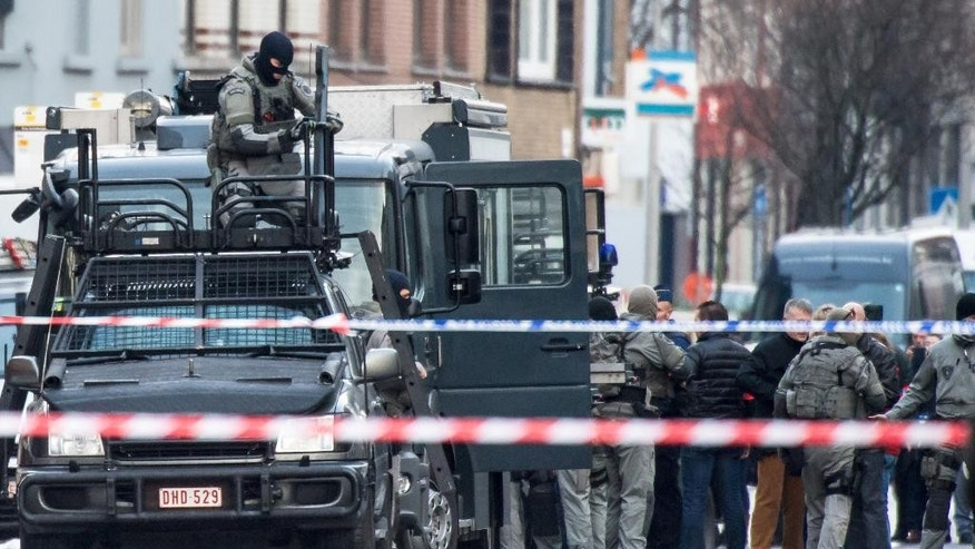A member of the special forces police installs equipment on a van, in Ghent, western Belgium, Monday, Dec. 15, 2014. Four armed men have entered an apartment, and police have blocked off a wide perimeter around the area. Police said Monday that three hours after the men entered the apartment it was still unclear whether they had taken any hostages. (AP Photo/Geert Vanden Wijngaert)