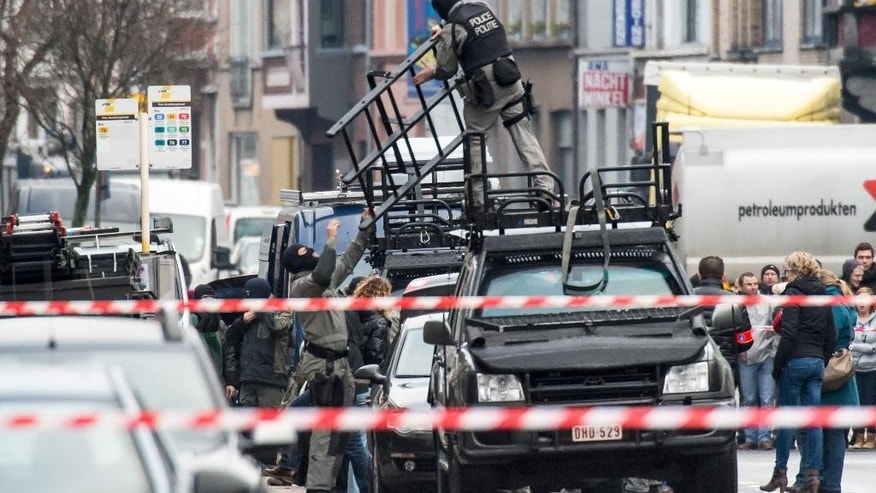 Special forces police install special equipment on a van, in Ghent, western Belgium, Monday, Dec. 15, 2014. Four armed men have entered an apartment, and police have blocked off a wide perimeter around the area. Police said Monday that three hours after the men entered the apartment it was still unclear whether they had taken any hostages. (AP Photo/Geert Vanden Wijngaert)