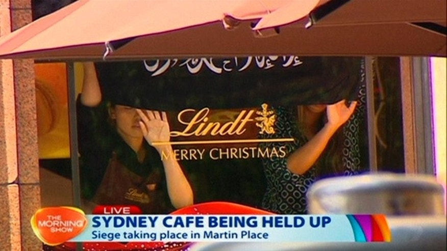 December 15, 2014: This image taken from video shows people holding up what appeared to be a black flag with white Arabic writing on it, inside a cafe in Sydney, Australia. (AP Photo/Channel 7 via AP Video)