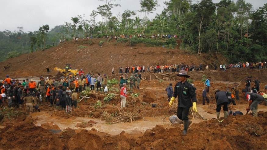 Dec. 14, 2014 - Rescuers search for the victims of a landslide that swept away a village in Jemblung, Central Java, Indonesia. The death toll rose to 56 Monday before rain forced rescuers to halt their search for dozens of missing people, officials said.