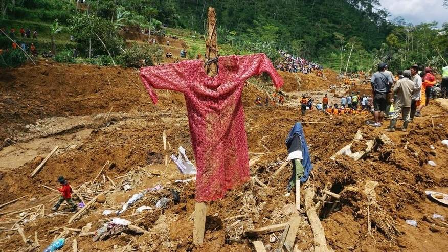 Rescuers search for the victims of a landslide that swept away a village in Jemblung, Central Java, Indonesia, Monday, Dec. 15, 2014. About 2,000 rescuers, including soldiers, police and volunteers, have been mobilized to dig through the mud and wreckage after the landslide Friday buried more than 100 houses and left dozens of people dead or missing. (AP Photo)
