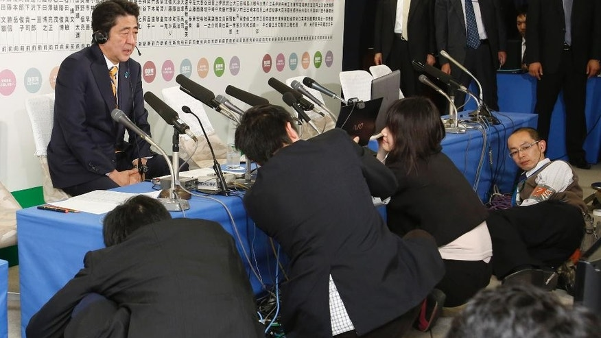 Japanese Prime Minister Shinzo Abe, left, speaks during a TV interview on ballot counting for the lower house elections at his Liberal Democratic Party headquarters in Tokyo, Sunday, Dec. 14, 2014. (AP Photo/Shizuo Kambayashi)