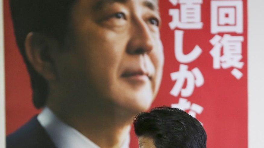 Japanese Prime Minister and leader of the ruling Liberal Democratic Party,  Shinzo Abe leaves after his press conference in Tokyo, Monday, Dec. 15, 2014. With a decisive victory last weekend in an election he forced by dissolving the lower house, the 60-year-old Abe has reaffirmed his hold on power. (AP Photo/Koji Sasahara)