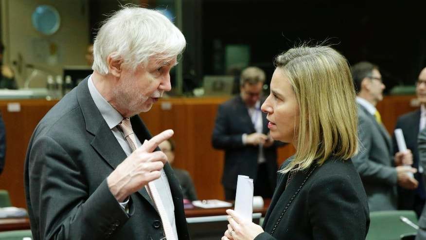 EU Foreign Policy Chief Federica Mogherini, right, talks with Finland's Foreign Minister Erkki Sakari Tuomioja, at the European Council building in Brussels, Monday, Dec. 15, 2014. European Union foreign ministers are discussing how they can help implement a U.N. plan to freeze fighting in the northern Syrian city of Aleppo. (AP Photo/Yves Logghe)