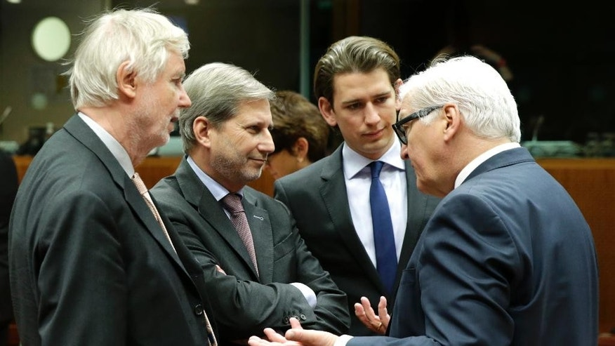 German Foreign Minister Frank-Walter Steinmeier, right, talks with European Commissioner for European Neighbourhood Policy and Enlargement Johannes Hahn, second left, Finland's Foreign Minister Erkki Sakari Tuomioja, left, and Austrian Foreign Minister Sebastian Kurz, at the European Council building in Brussels, Monday, Dec. 15, 2014. European Union foreign ministers met to discuss how they can help implement a U.N. plan to freeze fighting in the northern Syrian city of Aleppo. (AP Photo/Yves Logghe)