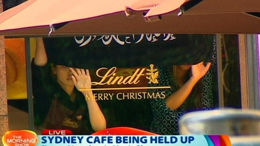 This image taken from video shows people holding up what appeared to be a black flag with white Arabic writing on it, inside a cafe in Sydney, Australia Monday, Dec. 15, 2014. A hostage siege in Sydney that began Monday morning and ended with a police raid 16 hours later unfolded before the world on Monday. (AP Photo/Channel 7 via AP Video) AUSTRALIA OUT
