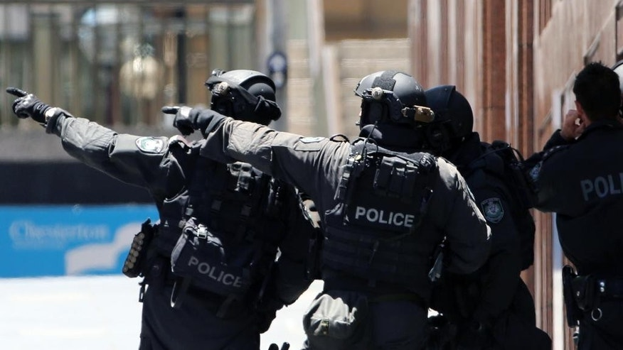 Armed police officers point as they stand at the ready close to a cafe under siege at Martin Place in Sydney, Australia, Monday, Dec. 15, 2014. The standoff at the cafe left three people dead, including the gunman, and four others wounded. (AP Photo/Rob Griffith)