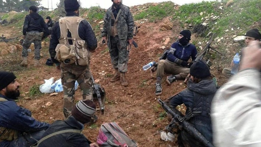 This Sunday, Dec. 14, 2014 photo provided by the anti-government activist group Syrian Observatory for Human Rights, which has been authenticated based on its contents and other AP reporting, shows Jihadi fighters from the al-Qaida-linked Nusra Front and other rebel factions, rest after clashes with Syrian troops in Wadi Deif in the northwestern province of Idlib, Syria. Jihadi fighters captured a Syrian army base Monday in the northwestern province of Idlib after two days of intense fighting that killed at least two dozen gunmen, activists said. (AP Photo/Syrian Observatory for Human Rights)