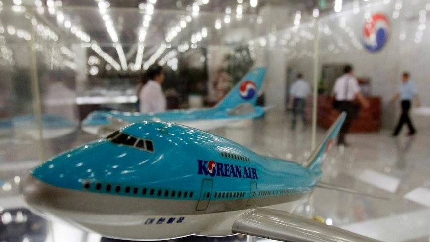 FILE - In this Aug. 14, 2009 file photo, customers walk near the model planes of Korean Air in a showroom at the headquarters of Korean Air Lines Co. in Seoul, South Korea. South Korea's transport ministry said Tuesday, Dec. 16, 2014 Korean Air Lines Co. will face sanctions for pressuring employees to lie during a government probe into the nut rage incident. Cho Hyun-ah, the daughter of Korean Air's chairman, ordered a crew member off a Dec. 5 flight, forcing it to return to the gate, after she was served macadamia nuts in a bag, instead of on a plate. (AP Photo/Lee Jin-man, File)