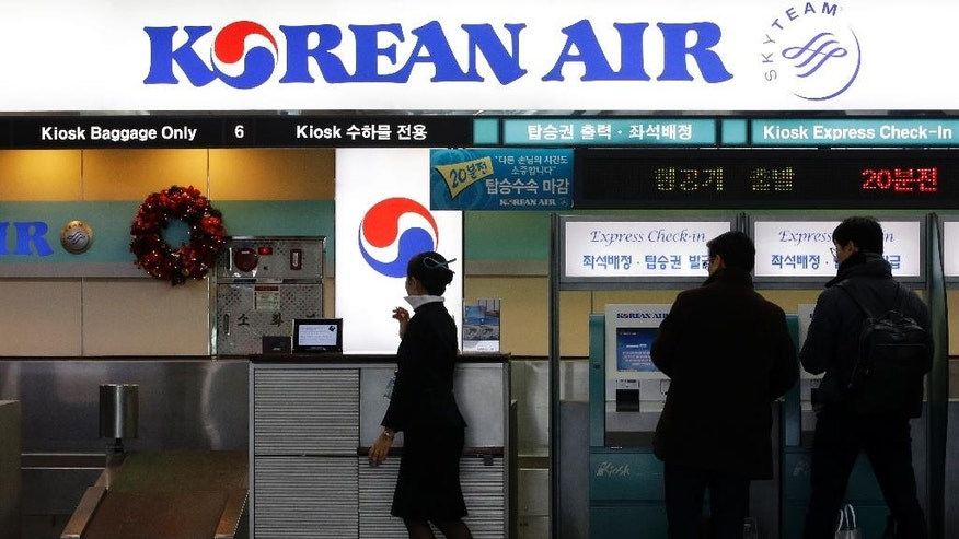 Passengers, right, are helped by an employee to check in at a Korean Air ticketing counter at Gimpo Airport in Seoul, South Korea, Tuesday, Dec. 16, 2014. South Korea's transport ministry said Korean Air Lines Co. will face sanctions for pressuring employees to lie during a government probe into the nut rage fiasco that highlighted the tyrannical behavior of a top Korean business family. (AP Photo/Lee Jin-man)