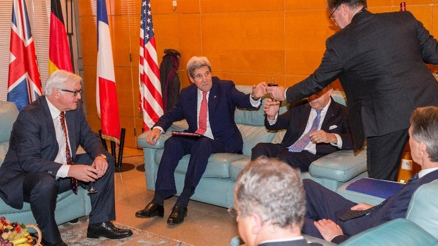 US Secretary of State John Kerry, second left, is served a drink before talks with German Foreign Minister Frank-Walter Steinmeier, left, French Foreign Minister Laurent Fabius, center right sitting, and British Foreign Minister Philip Hammond, right sitting, in Paris on Monday Dec. 15, 2014. Secretary of State John Kerry met Monday with Israeli Prime Minister Benjamin Netanyahu as the U.S. and Israel developed their responses to a draft U.N. resolution that would set a two-year timetable for an Israeli-Palestinian peace accord. (AP Photo/Evan Vucci, Pool)