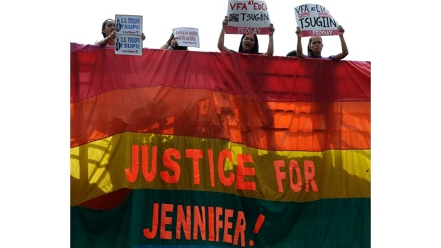 Dec. 1, 2014: Protesters hang a rainbow banner from the foot bridge near the U.S. Embassy to demand justice for the killing of Filipino transgender Jennifer Laude at the former US naval base of Subic northwest of Manila. (AP Photo/Bullit Marquez)