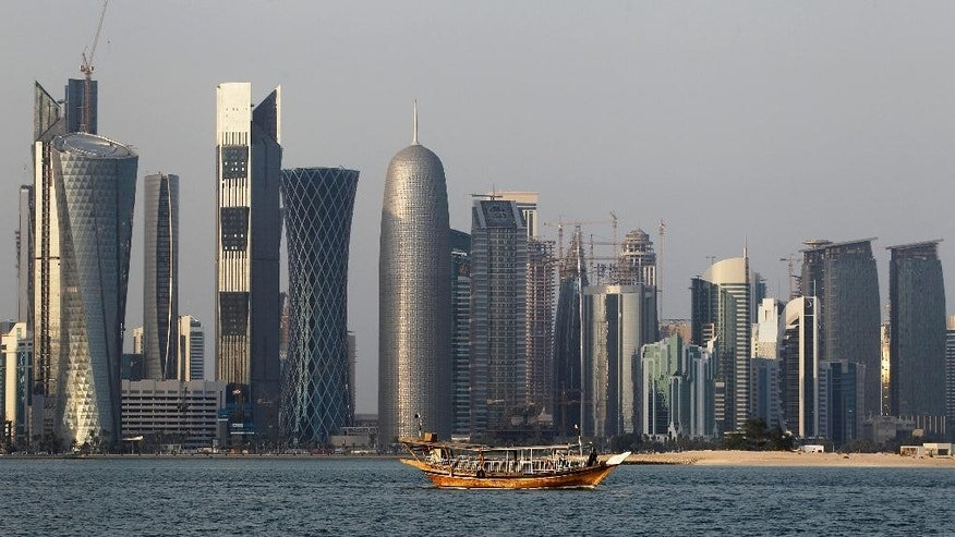 FILE - In this Thursday Jan. 6, 2011 file photo, a traditional dhow floats in the Corniche Bay area with tall buildings of the financial district in the background. The 2022 World Cup in Qatar, the wealthy oil- and gas-producing Gulf nation with giant look-at-me ambitions that belie its small size, is shaping up as a unique experience. (AP Photo/Saurabh Das, File)