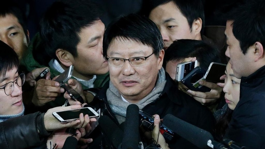 Park Ji-man, South Korean President Park Geun-hye's brother, center, talks to the media upon his arrival at Seoul District Prosecutors' Office in Seoul, South Korea, Monday, Dec. 15, 2014. Prosecutors hauled in Park for questioning, the latest in a slew of high-profile figures who have been summoned since a local newspaper first reported the speculation late last month.(AP Photo/Ahn Young-joon)