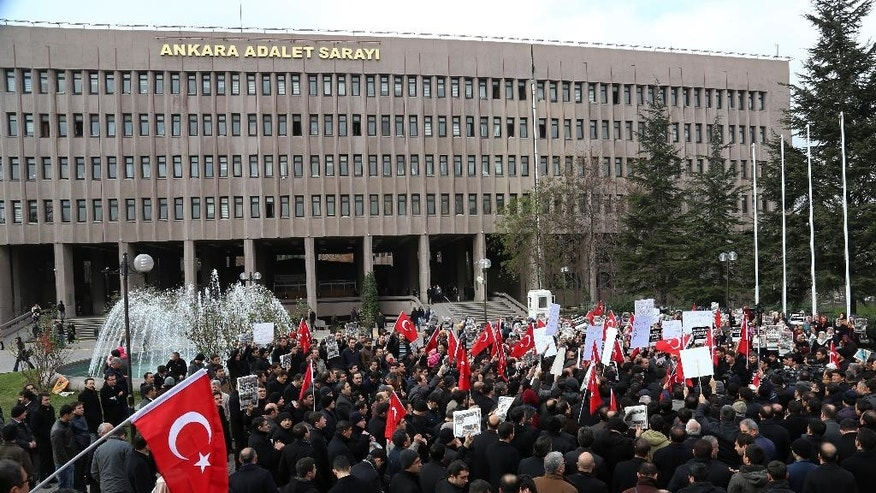 People gather outside the  Palace of Justice  in Ankara, Turkey, Monday, Dec. 15, 2014 to protest against the latest detentions of journalists. Police conducted raids in a dozen Turkish cities Sunday, detaining at least 32 people — including journalists, TV producers and police — known to be close to a movement led by a U.S.-based moderate Islamic cleric who is a strong critic of President Recep Tayyip Erdogan. It was the latest crackdown on cleric Fethullah Gulen's movement, which the government has accused of orchestrating an alleged plot to try to bring it down.(AP Photo)
