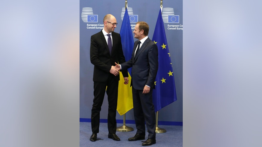 European Council President Donald Tusk, right, welcomes Ukrainian Prime Minister Arseniy Yatsenyuk, ahead of a meeting at the European Council building in Brussels, Monday, Dec. 15, 2014. (AP Photo/Yves Logghe)