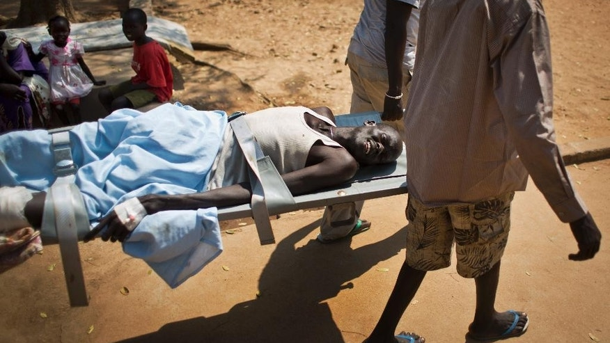 FILE In this Saturday Dec. 28 2013 file photo, a man with a gunshot wound in his leg is carried by stretcher from one ward to another inside the Juba Military Hospital in Juba, South Sudan. One year after mass violence broke out in South Sudan, battles between government forces and rebel fighters continue, and aid officials say the international community must help residents stave off mass hunger. (AP Photo/Ben Curtis, File)
