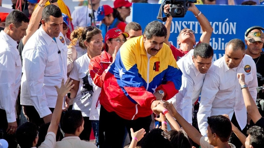 Venezuela's President Nicolas Maduro, center, surrounded by bodyguards, shakes hands with supporters during an anti USA march in Caracas, Venezuela, Monday, Dec. 15, 2014. Thousands of government supporters and public employees marched in opposition to sanctions the U.S. Congress targeted at a group of Venezuelan officials accused of human rights violations and to commemorate the 15 years of the adoption of the new Venezuelan Constitution. (AP Photo/Fernando Llano)