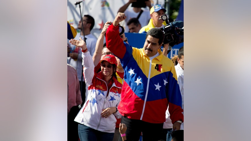 Venezuela's President Nicolas Maduro, right, and his wife Cilia Flores greets supporters upon their arrival for a speech during an anti USA march in Caracas, Venezuela, Monday, Dec. 15, 2014. Thousands of government supporters and public employees marched in opposition to sanctions the U.S. Congress targeted at a group of Venezuelan officials accused of human rights violations and to commemorate the 15 years of the adoption of the new Venezuelan Constitution. (AP Photo/Fernando Llano)