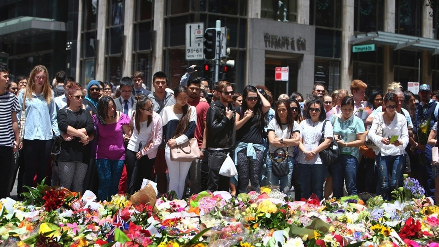 Dec. 16, 2014: Staff members from the Lindt Chocolat Cafe with their arms linked pay tribute to their colleague who lost his live during a siege at the popular coffee shop at Martin Place in the central business district of Sydney, Australia.