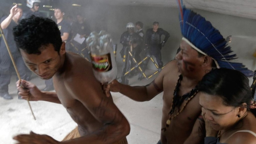 Indians from various tribes run from tear gas fired by police after they tried to enter the Chamber of Deputies where lawmakers are debating the authority to demarcate indigenous lands at Congress in Brasilia, Brazil, Tuesday, Dec. 16, 2014. Brazil's indigenous don't agree with a proposed constitutional amendment that would allow Congress to decide their ancestral lands' legal borders, in place of the Ministry of Justice with whom negotiations had already started years ago. Brazilians are legally allowed to watch lawmakers' debate, but police at the scene said they didn't let the indigenous to enter on suspicion that they would interrupt the debate. (AP Photo/Eraldo Peres)