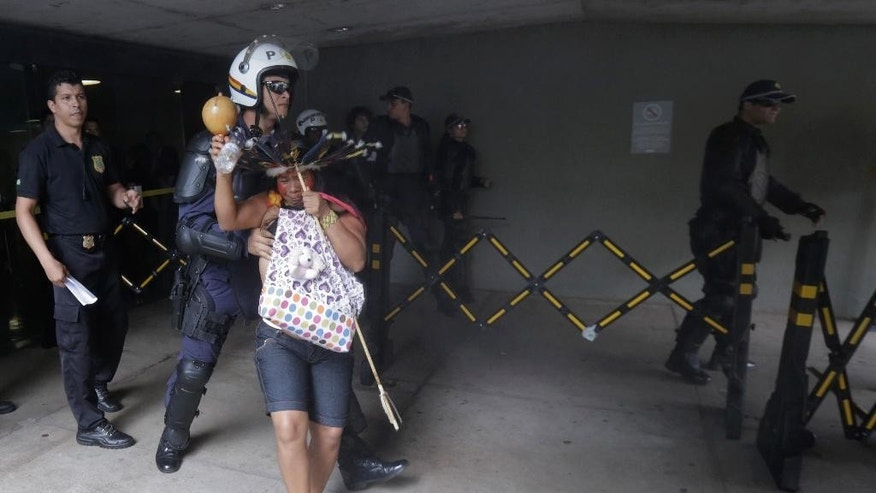 A police officer pushes an indigenous woman away from the entrance to the Chamber of Deputies where lawmakers are debating the authority to demarcate indigenous lands at Congress in Brasilia, Brazil, Tuesday, Dec. 16, 2014. Brazil's indigenous don't agree with a proposed constitutional amendment that would allow Congress to decide their ancestral land's legal borders, in place of the Ministry of Justice with whom negotiations had started years ago. Brazilians are legally allowed to watch lawmakers' debate, but police at the scene said they didn't allow a group of indigenous to enter on suspicion they would interrupt the debate. (AP Photo/Eraldo Peres)