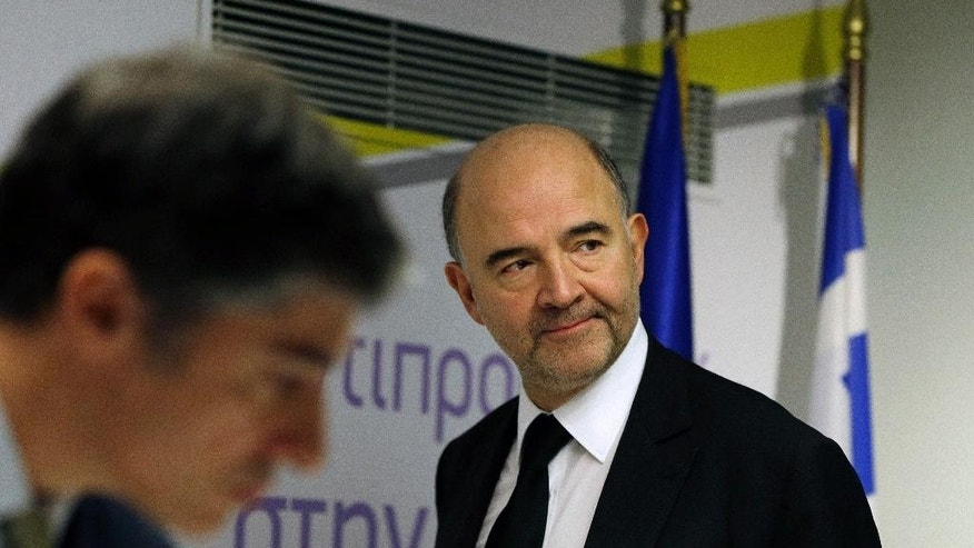 "EU Commissioner for Economic and Financial Affairs Pierre Moscovici arrives at a news conference in Athens on Tuesday, Dec. 16, 2014. A refusal by Greece to repay bailout debts would be ""suicidal"" for the country, the European Union's top finance official said Monday in a clear warning to the country's popular opposition. Moscovici's two-day visit went ahead despite stalled negotiations between Greece and bailout creditors, and took place ahead of a parliamentary vote that could topple Greece's pro-bailout government this month. (AP Photo/Thanassis Stavrakis)"