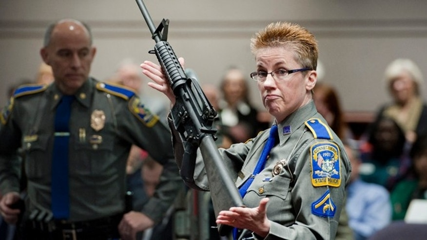 FILE - In this Jan. 28, 2013, file photo, firearms training unit Detective Barbara J. Mattson, of the Connecticut State Police, holds up a Bushmaster AR-15 rifle, the same make and model of gun used by Adam Lanza in the Sandy Hook School shooting, for a demonstration during a hearing of a legislative subcommittee reviewing gun laws, at the Legislative Office Building in Hartford, Conn. The families of nine of the 26 people killed and a teacher injured on Dec. 14, 2012, at the Sandy Hook Elementary School filed a lawsuit against the manufacturer, distributor and seller of the Bushmaster AR-15 rifle used by Lanza in the shooting. (AP Photo/Jessica Hill, File)