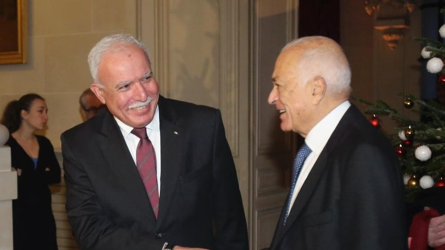 Palestinian foreign minister Riyad al-Maliki, left, shakes hand with Arab League secretary general Nabil Al-Arabi, right, prior to a meeting with French foreign minister Laurent Fabius, at the Quai d'Orsay in Paris, Tuesday Dec. 16, 2014. France is trying to overcome resistance and rally international support for a draft U.N. plan seeking a two-year deadline for peace talks on Palestinian statehood. (AP Photo/Remy de la Mauviniere)