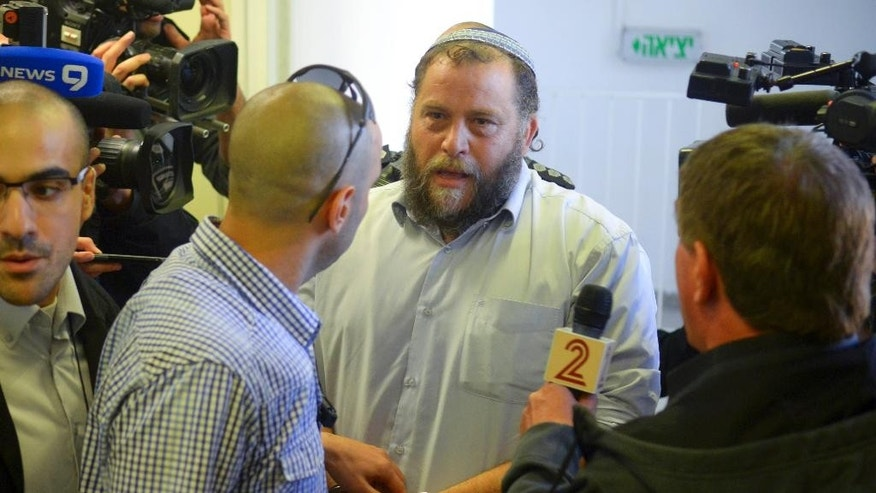 Bentzi Gopstein, leader of the extreme right-wing movement Lehava, is handcuffed as he arrives for his hearing at a Jerusalem Court, Tuesday, Dec. 16, 2014. Israeli police on Tuesday arrested 10 Jewish activists from an extremist group opposed to Arab-Jewish coexistence, including its leader, in the first major clampdown against a fringe organization that has become a symbol of rising anti-Arab sentiment. (AP Photo/Mahmoud Illean)