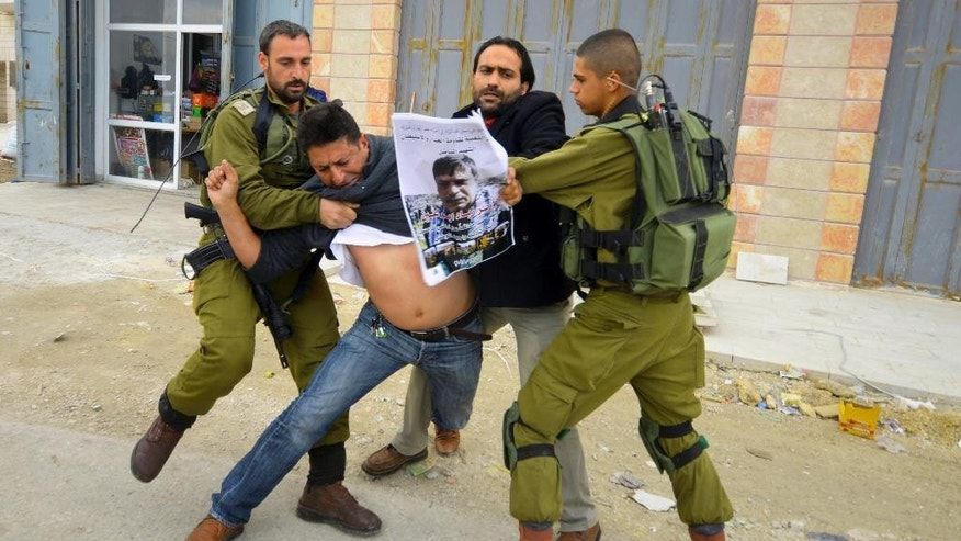 In this Friday, Dec. 12, 2014 photo, Israeli soldiers grab a Palestinian holding a poster showing late Cabinet minister Ziad Abu Ain during a protest in Bethlehem, West Bank. Abu Ain  collapsed and died shortly after scuffling with Israeli troops during a West Bank protest Wednesday. (AP Photo/Mahmoud Illean)