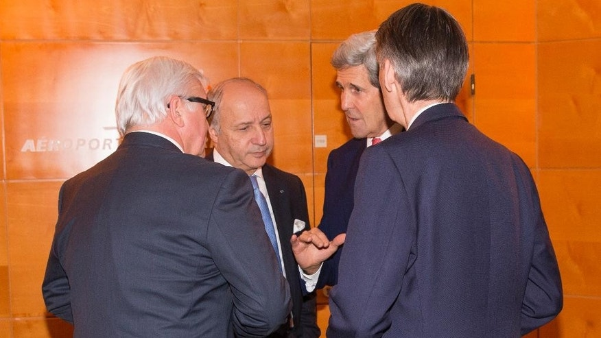 US Secretary of State John Kerry, third left, talks with German Foreign Minister Frank-Walter Steinmeier, left, French Foreign Minister Laurent Fabius, second left, and British Foreign Minister Philip Hammond in Paris on Monday Dec. 15, 2014. Secretary of State John Kerry met Monday with Israeli Prime Minister Benjamin Netanyahu as the U.S. and Israel developed their responses to a draft U.N. resolution that would set a two-year timetable for an Israeli-Palestinian peace accord. (AP Photo/Evan Vucci, Pool)