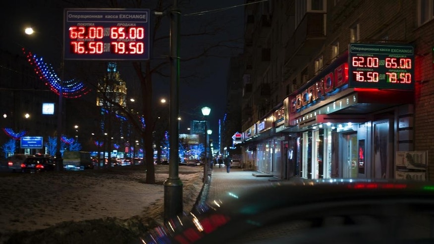 Signs advertising currencies light next to the exchange office in Moscow, Russia, Monday, Dec. 15, 2014. The price of crude oil continued to drop Monday, and Russia's ruble plunged to a record low against the dollar. The ruble crashed through 60 to the dollar, trading at 60.33 by early afternoon.(AP Photo/Pavel Golovkin)