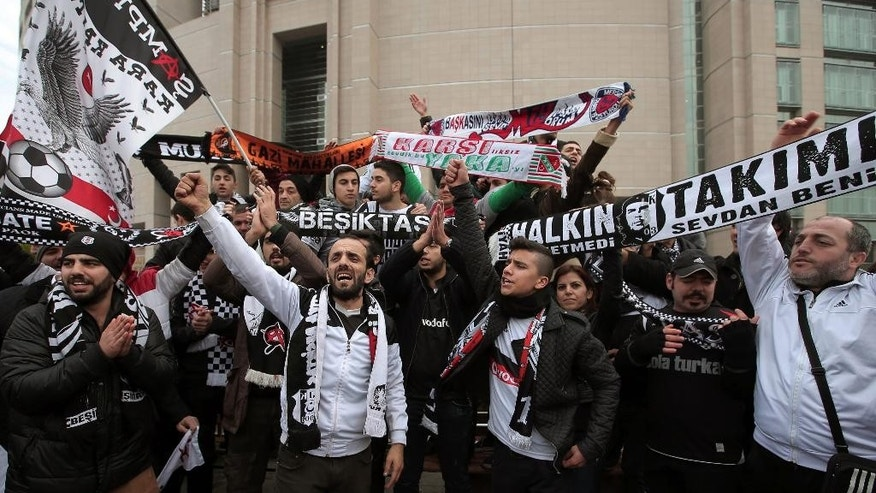 Cheering fans of Besiktas, a leading Turkish soccer team, gather outside a courthouse as the trial of dozens of football fans began in Istanbul, Turkey, Tuesday, Dec. 16, 2014. Besiktas fans are accused of an attempted coup because they took part in last year's mass protests against the government's plans to redevelop Gezi Park adjacent to Istanbul's main Taksim Square. The trial is seen as the latest example of President Recep Tayyip Erdogan's crackdown on dissent.(AP Photo/Emrah Gurel)