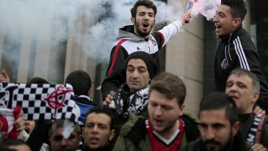 Cheering fans of Besiktas, leading Turkish soccer team, gather outside a courthouse as trial of dozens of football fans begun in Istanbul, Turkey, Tuesday, Dec. 16, 2014. Besiktas fans are accused of an attempted coup because they took part in last year's mass protests against government's plans to redevelop Gezi Park adjacent to Istanbul's main Taksim Square. The trial is seen as the latest example of President Recep Tayyip Erdogan's crackdown on dissent.(AP Photo/Emrah Gurel)