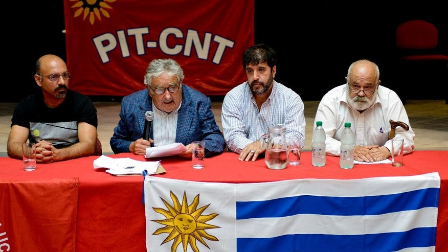 "Uruguay's President Jose Mujica, second left, speaks surrounded by labor leaders Marcelo Abdala, left, Marcelo Pereira, second right, and Defense Minister Eluterio Fernandez, right, during a press conference at the workers union PIT-CNT in Montevideo, Uruguay, Tuesday, Dec. 16, 2014. Mujica says the United States has guaranteed that six former Guantanamo Bay prisoners who arrived in Uruguay as refugees are not terrorists. He showed a document from the U.S. State Department saying there's no information that ""the men were involved in conducting or facilitating terrorist activities"" against the U.S., its partners or allies. Members of Uruguay's opposition had requested the release of the documents. (AP Photo/Matilde Campodonico)"